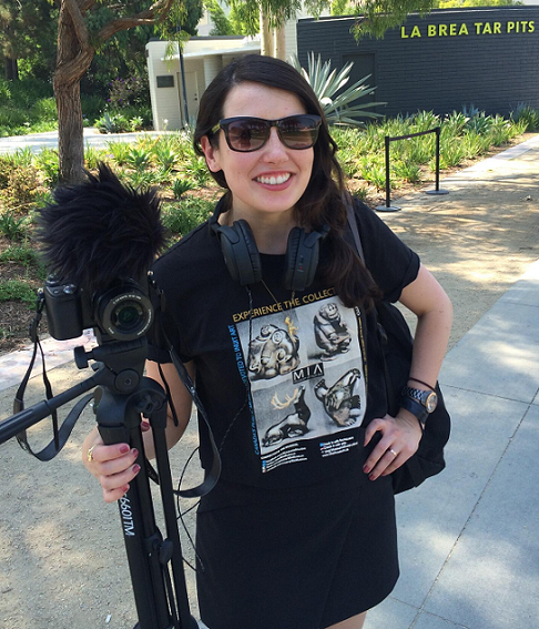 Cristina Russo, program manager at NCI CBIIT, holding film equipment in front of La Brea Tar Pits.