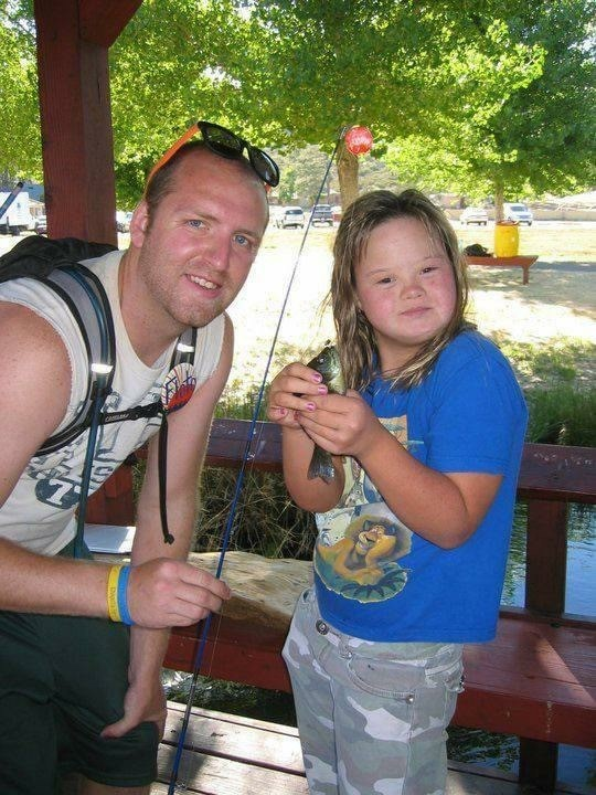 Joe helps a young camper bait her fishing pole
