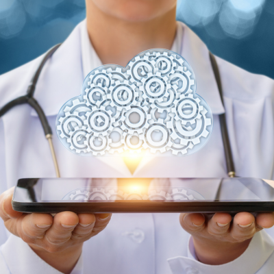 Doctor wearing stethoscope holding tablet with graphic of a cloud above, depicting cloud computing.