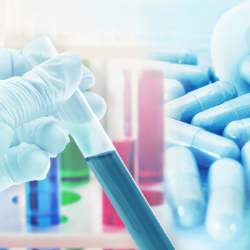 Image of gloved hand holding a test tube filled with blue liquid; in the background are pills, making the association between research and drug development.