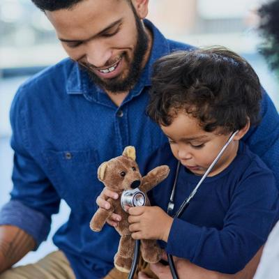 Male child uses stethoscope to listen for teddy bear's pulse. Child sits on adult male's lap.