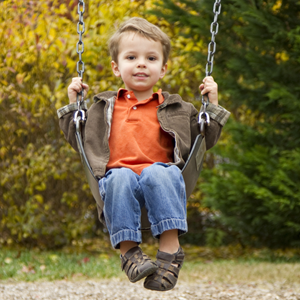 Young boy in orange shirt on swing in park