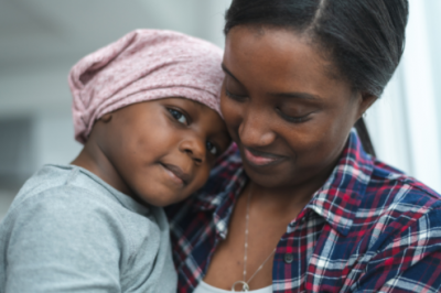 Smiling Black mother holding her young Black child to her chest; child has her head on mother's shoulder and is wearing a pink bandanna around her head.